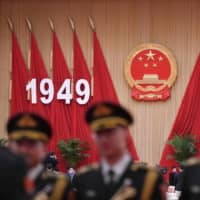 Members of a Chinese military band pose for photos before a reception at the Great Hall of the People in Beijing on the eve of China's National Day on Sept. 30. | AFP-JIJI