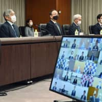 Bank of Japan Gov. Haruhiko Kuroda (left, front) holds an online meeting with the bank's regional managers on Thursday.  | POOL / VIA KYODO