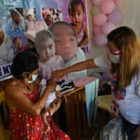 A municipal health worker applies drops of a polio vaccine for a child in San Jose Del Monte, north of Manila, in September. | AFP-JIJI