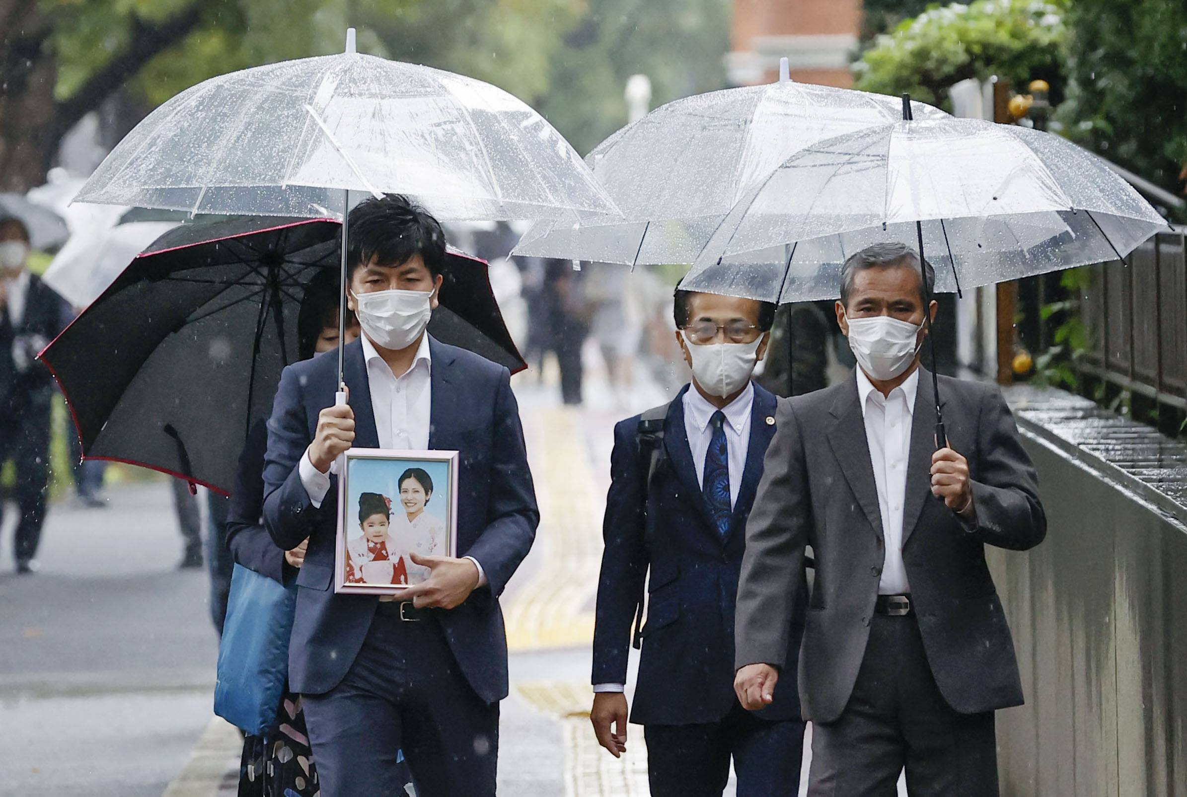 Takuya Matsunaga holds a picture of his wife and daughter as he heads to the Tokyo District Court Thursday for a trial over the fatal traffic accident.  | KYODO