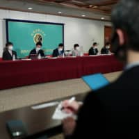 Industry experts who spearheaded a report by the Asia Pacific Initiative on the government's response to COVID-19 speak during a news conference at the Japan National Press Club in Tokyo on Thursday. | RYUSEI TAKAHASHI