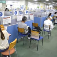 Job-seekers wait for consultation at a public employment service in Tokyo's Shibuya Ward in June. When the economy started reopening, portions of the population were left behind, such as laid-off workers or those who continued to be stuck at home. | KYODO