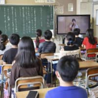 Students attend class in August at an elementary school in Yokohama. Schools restarted in June after a three-month closure, which saw an increase in reports of bullying and added stress about catching up on schoolwork. | KYODO