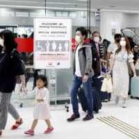 An arrival lobby at Tokyo's Haneda Airport is crowded with people Sunday, on the first weekend after the capital was added to the Go To Travel campaign to shore up domestic tourism. | KYODO