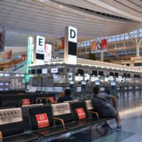 Social distancing signs on benches at Haneda Airport in Tokyo in July | BLOOMBERG
