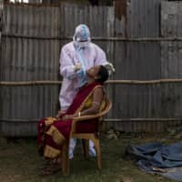 A health worker performs a coronavirus test in Masli, in the state of Tripura, India.  | ANINDITO MUKHERJEE / THE NEW YORK TIMES