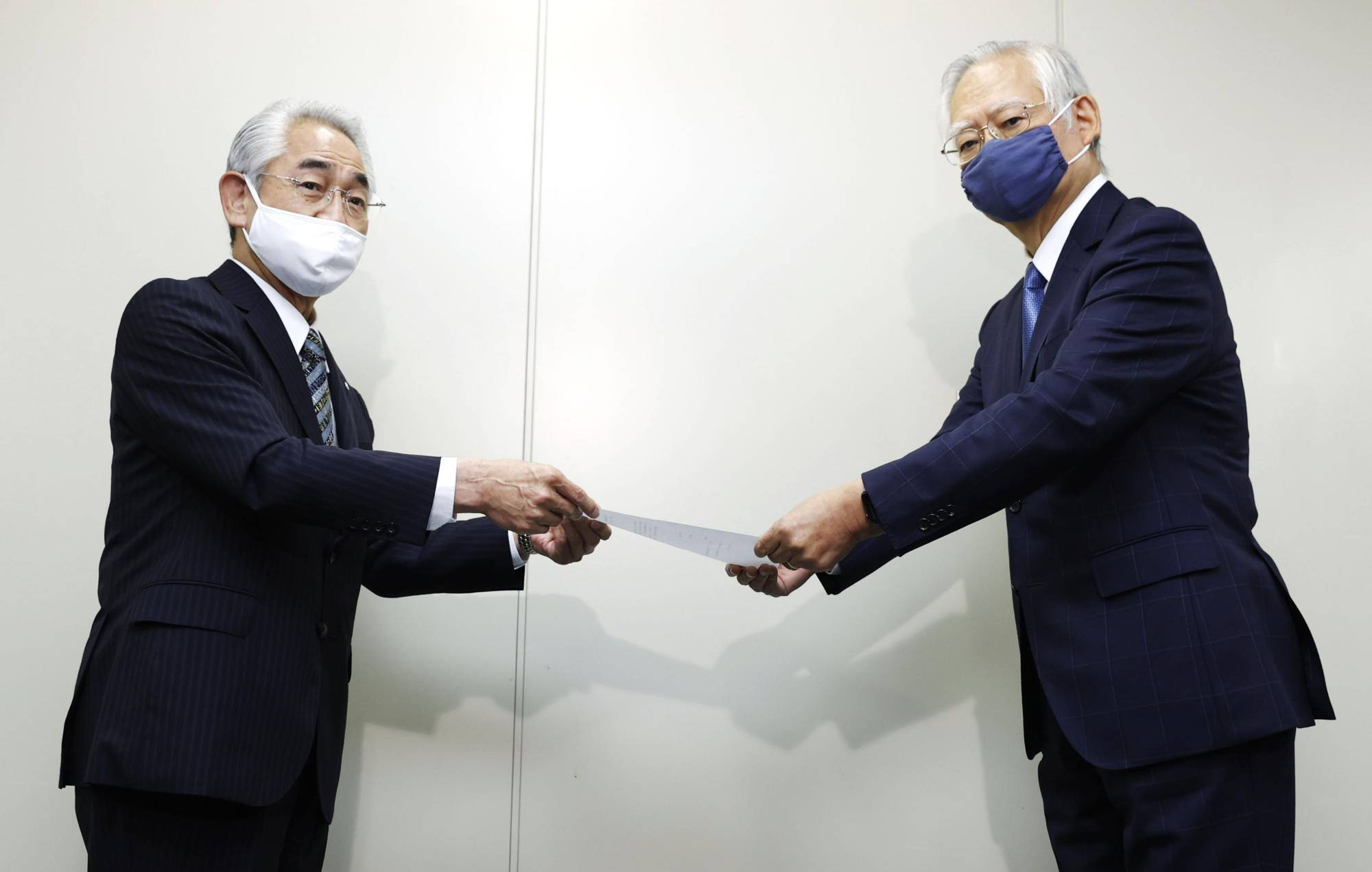 Haruo Kataoka (left), mayor of Suttsu in Hokkaido, submits the documents to apply for a nuclear waste disposal site survey to Shunsuke Kondo, head of the Nuclear Waste Management Organization, in Tokyo on Friday. | KYODO
