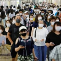Passengers wearing protective face masks make their way to work amid the COVID-19 pandemic in September. | REUTERS
