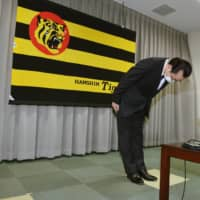 Tigers president Kenji Ageshio bows during a news conference in Nishinomiya, Hyogo Prefecture, on Friday. | POOL / VIA KYODO