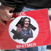 A demonstrator carries a protest poster of Michigan Gov. Gretchen Whitmer during a Michigan Conservative Coalition organized protest outside the Michigan State Capitol in Lansing on May 20. | AFP-JIJI