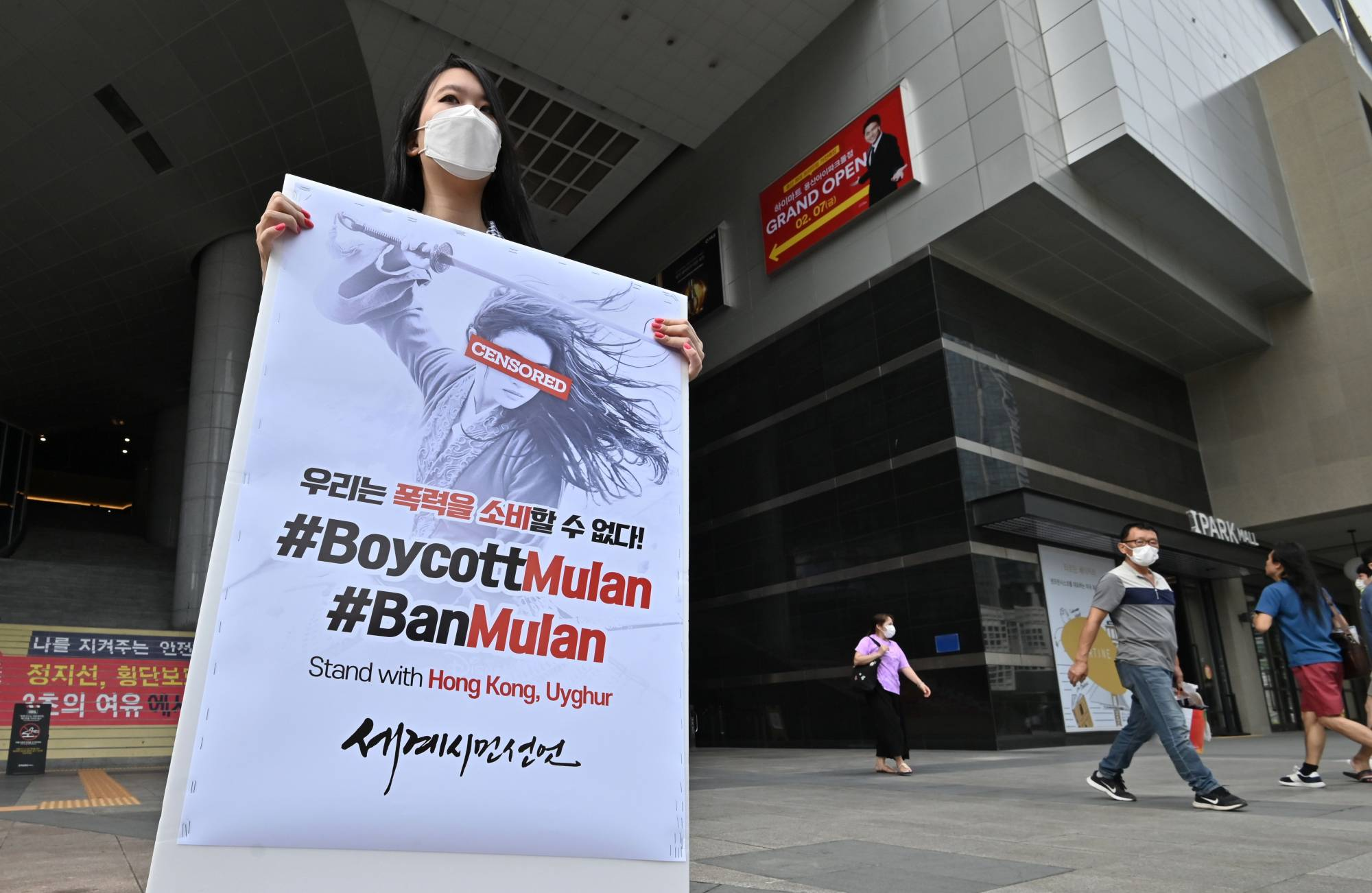 A South Korean protester holds a placard during a lone protest against the release of the Disney movie 'Mulan' outside a movie theater in Seoul on Sept. 17. | AFP-JIJI