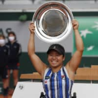 Yui Kamiji lifts the trophy after winning the women's wheelchair final at the French Open on Friday in Paris. Kamiji defeated Momoko Ohtani in an all-Japanese final. | AP