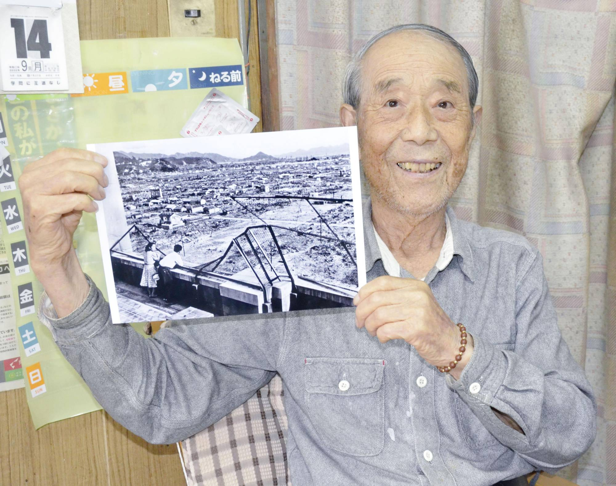 Kiyoshi Kawaue, 90, holds a photograph of him and his late wife looking out over the city of Hiroshima from the top of a building a year after the city was destroyed by a nuclear bomb in 1945.   KYODO