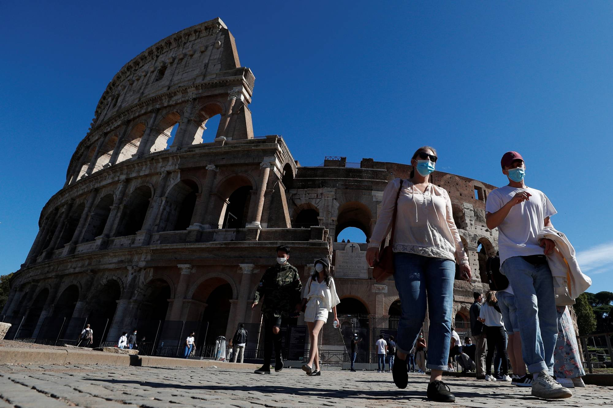 People wearing protective face masks walk past the Colosseum as local authorities in Rome ordered face coverings to be worn at all times outdoors. | REUTERS