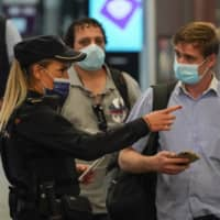 A police officer checks the documents of a passenger inside Atocha railway station in Madrid on Friday, the day the government declared a state of emergency for the Spanish capital.  | BLOOMBERG