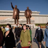 People leave after paying their respects before the statues of late North Korean leaders Kim Il Sung and Kim Jong Il at Mansu Hill, as the country marks the 75th founding anniversary of the Workers' Party of Korea, in Pyongyang on Saturday. | AFP-JIJI