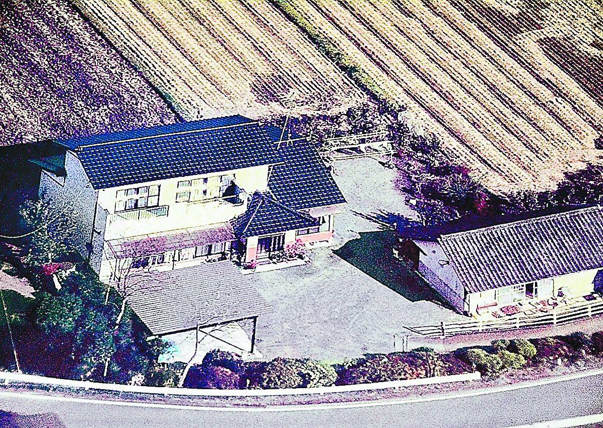 A September 2009 photo shows the home of Takashi Asano in Okuma, Fukushima Prefecture. The house is now a wreck with a damaged roof and is accessible to wild animals. | FUKUSHIMA MINPO
