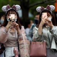 Visitors take photos at Tokyo Disneyland. A new study highlights COVID-19 transmission risk from touchscreen devices.  | REUTERS