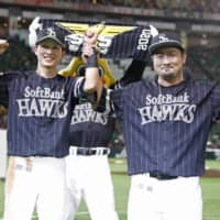The Hawks' Ukyo Shuto (left) and Yuito Mori celebrate after their win over the Marines on Sunday in Fukuoka. | KYODO