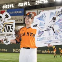 Tomoyuki Sugano poses for photos after recording the 100th victory of his career and his 13th straight since opening day this season on Oct. 6 at Tokyo Dome.  | KYODO