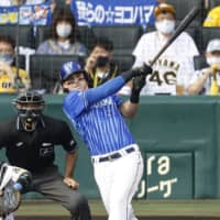 The BayStars' Tyler Austin hits a home run against the Tigers during the fourth inning on Saturday. | KYODO