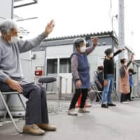 Residents in temporary housing in Marumori, Miyagi Prefecture, exercise last week. Nearly 8,000 people are still caught up in evacuee life as Japan marked the first anniversary Monday of Typhoon Hagibis' landfall.   KYODO