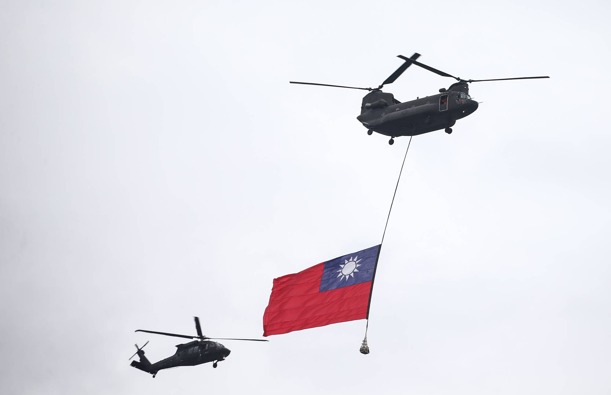 A helicopter flies overhead with a Taiwanese flag during National Day celebrations in Taipei on Saturday. Taiwan has labeled new spying accusations by China as fake news after Chinese state television aired a program showing a Taiwanese academic arrested in China on national security grounds. | BLOOMBERG