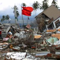 Men walk amid the debris of their devastated houses following the 2004 tsunami at a housing complex in Kajhu, on the outskirts of Banda Aceh, Indonesia, in 2005, | REUTERS