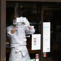 A staff member displays an 'open' sign on the door of a restaurant near Gora station in Hakone, Kanagawa Prefecture, on Oct. 4. The national Go To Travel campaign aimed at spurring domestic travel included Tokyo from this month. | BLOOMBERG