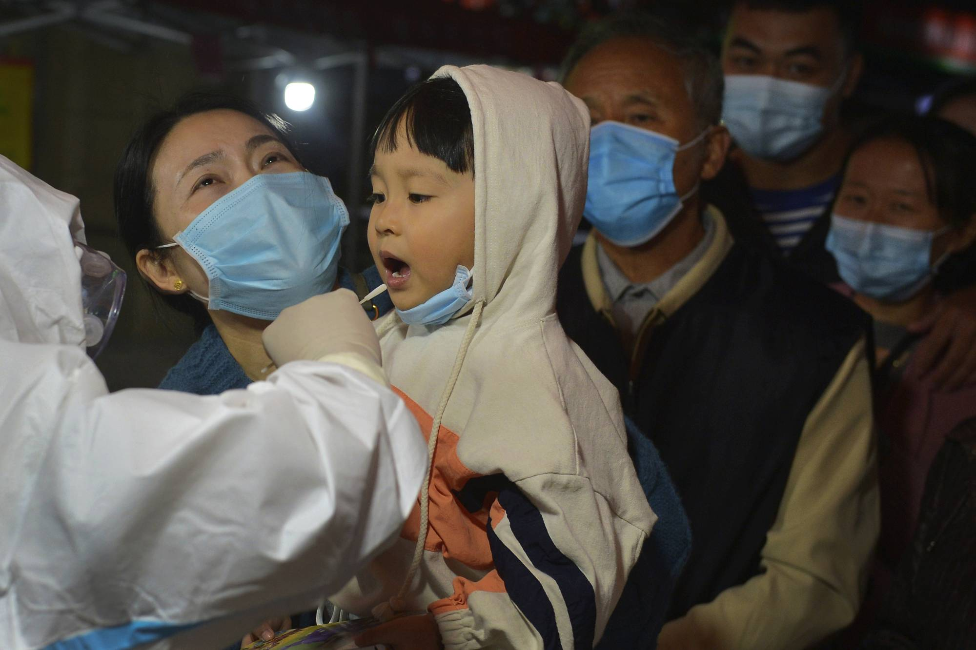 A child is tested for COVID-19 in Qingdao, in east China's Shandong province, on Monday.  | CHINATOPIX / VIA AP
