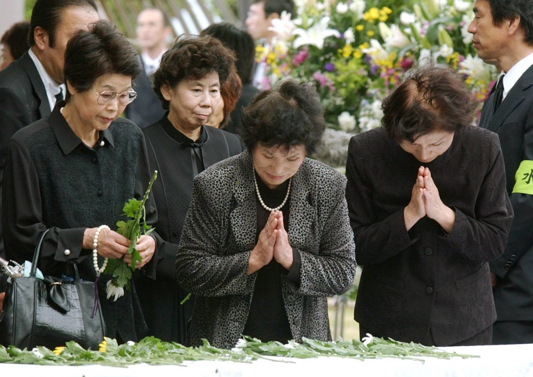 Attendees pray in Minamata, Kumamoto Prefecture, during a memorial ceremony in May 2006 to mark the 50th anniversary of Minamata disease being officially recognized.   KYODO
