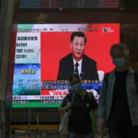 A live broadcast of Chinese President Xi Jinping delivering a speech in the city of Shenzhen is shown in Hong Kong on Wednesday.  | BLOOMBERG