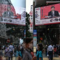 A news report on Chinese President Xi Jinping's speech in the city of Shenzhen is shown on a public screen in Hong Kong on Wednesday. | BLOOMBERG