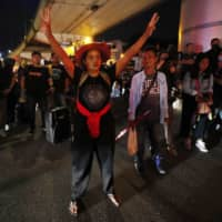 A pro-democracy protester raises a three-finger salute, a symbol of resistance, during a protest in Bangkok on Wednesday. | AP