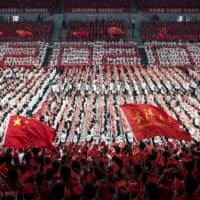First-year students wave Chinese flags during a commencement ceremony in China's Hubei province last month. | AFP-JIJI