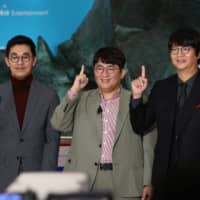 Bang Si-hyuk (center), founder of Big Hit Entertainment Co., and other executives pose at a ceremony for the company's IPO at the Korea Exchange in Seoul on Thursday.  | BLOOMBERG