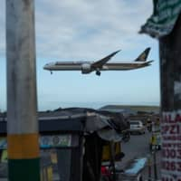 A Singapore Airlines aircraft prepares to land at Ninoy Aquino International Airport in Manila in February.  | BLOOMBERG