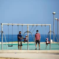 Parents play with their toddlers at a playground by the beach in Israel last month.  | REUTERS