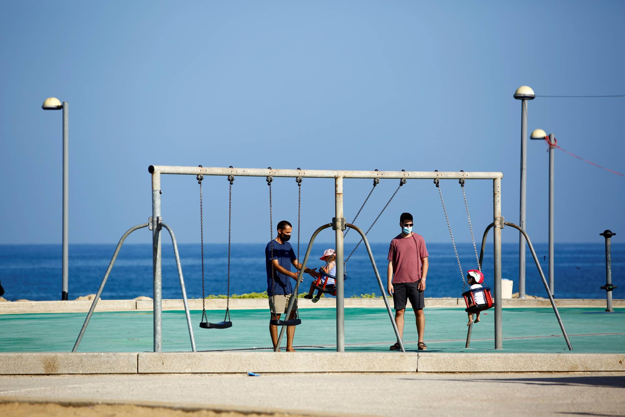 Parents play with their toddlers at a playground by the beach in Israel last month.    REUTERS