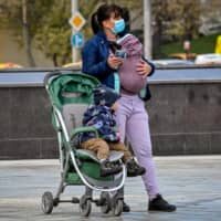 A mother and her babies wait for a bus in central Moscow last month.  | AFP-JIJI
