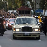 A vehicle carrying Thailand's King Maha Vajiralongkorn and Queen Suthida drives past an anti-government mass protest in Bangkok on Wednesday.  | REUTERS