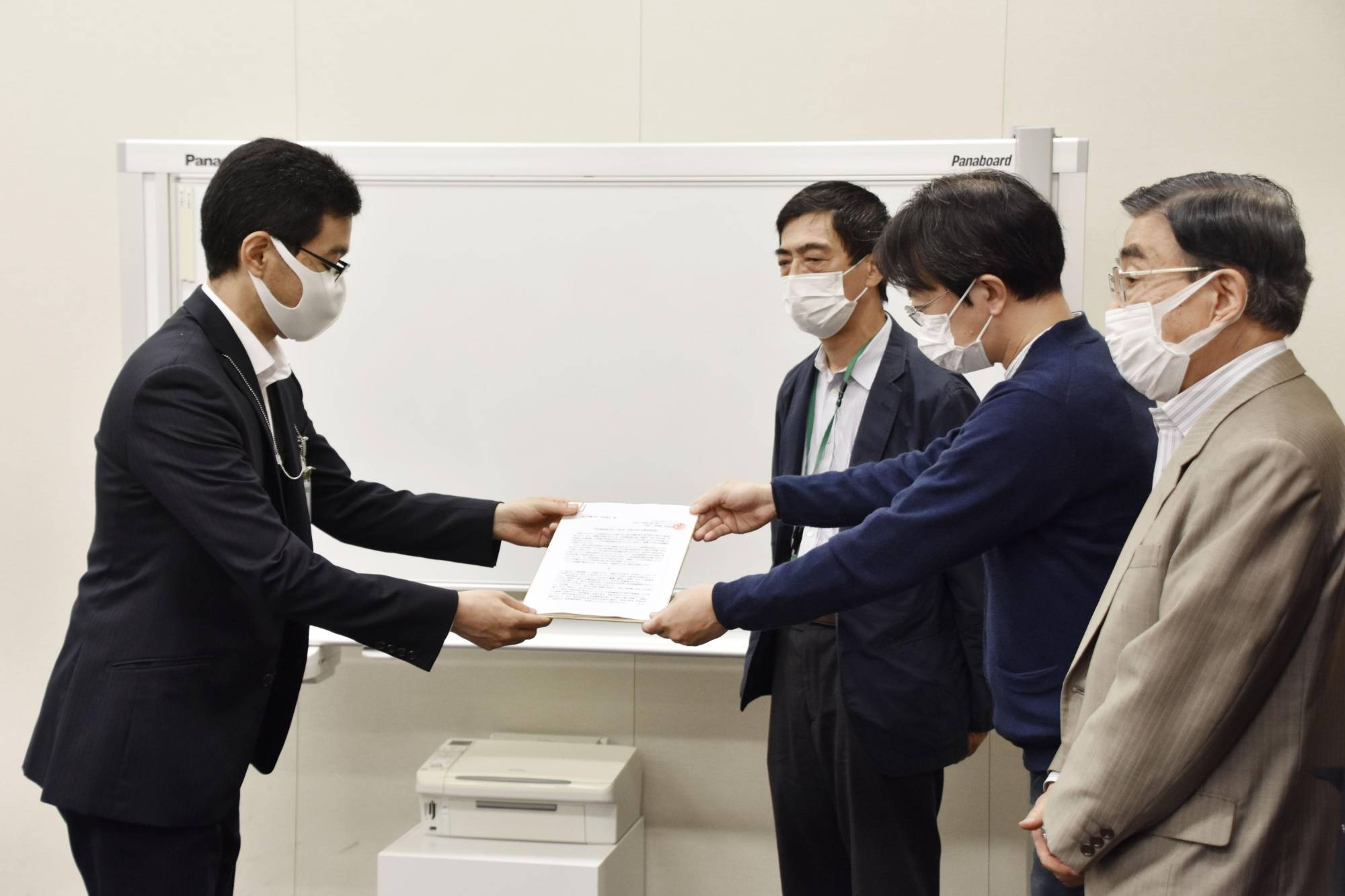 A support group representative hands in a petition for an extension of the duration of government rent support to an official of the welfare ministry in Tokyo last month.   KYODO