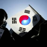 Protesters hold an anti-Japan rally in Seoul. Some 71.6% of South Koreans see Japan unfavorably, a survey shows.   GETTY IMAGES / VIA BLOOMBERG