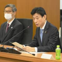 Yasutoshi Nishimura, minister in charge of coronavirus measures, speaks at a government subcommittee meeting in Tokyo on Thursday. On his left is the subcommittee head Shigeru Omi. | KYODO