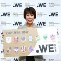 WE League Chair Kikuko Okajima holds a sign displaying the names of the league's founding 11 members following a Thursday news conference at JFA House in Tokyo's Bunkyo Ward. | WE LEAGUE