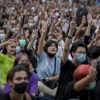 Pro-democracy protesters flash the three-fingered salute during a protest in Bangkok on Thursday.