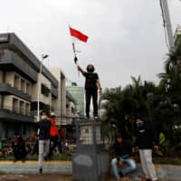 A demonstrators protest against the new so-called omnibus law in Jakarta on Tuesday. | REUTERS