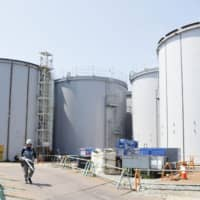 Tanks for storing treated water from which most of the radioactive contamination has been removed are seen at the Fukushima No. 1 nuclear power plant in Okuma, Fukushima Prefecture, in August. | KYODO