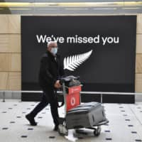 A passenger from New Zealand arrives at Sydney Airport on Friday after quarantine restrictions were lifted on travelers from New Zealand.  | AAP IMAGE / VIA AP