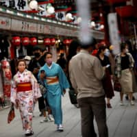 Kimono-clad tourists wearing protective face masks walk along Nakamise street in Tokyo's Asakusa district, a popular sightseeing spot, on Tuesday. | REUTERS